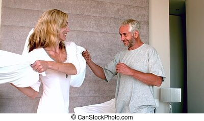 Mature couple having a pillow fight and laughing in slow...