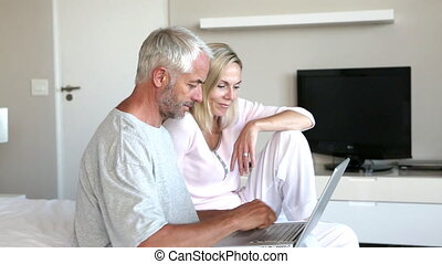 Couple using laptop together in the bedroom and smiling