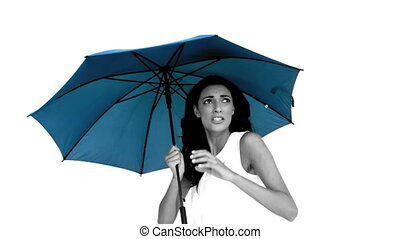 Woman under blue umbrella cowering