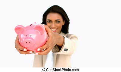 Businesswoman showing piggy bank to the camera in slow...