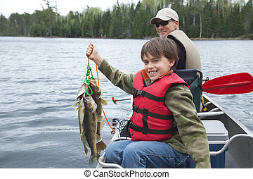 Young fisherman proudly holds stringer of walleyes - A young...