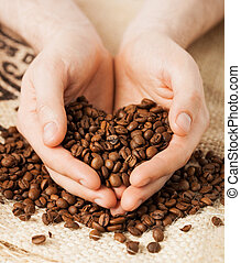 man holding coffee beans - close up of man holding coffee...