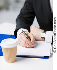 businessman with coffee writing something - businessman with...