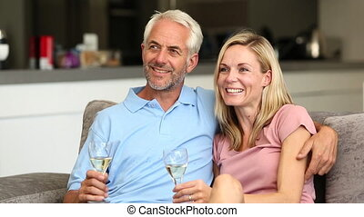 Couple watching tv while holding white wine glass in the...