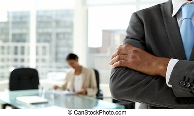 Businessman with crossed arms standing by desk in office
