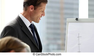 Confident businessman giving presentation of a graph as...