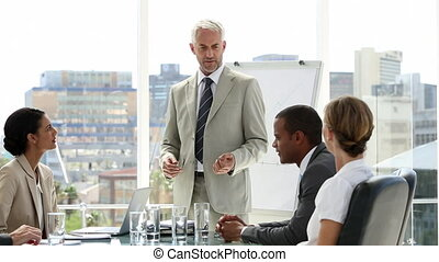 Businessman presenting to his team who applaud him in the...