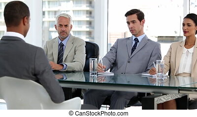 Business people interviewing a candidate in a bright office