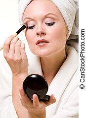 Putting on makeup - Attractive blond woman applying makeup...