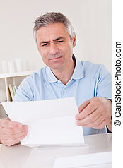 Horrified old man reading a letter - Horrified old man...