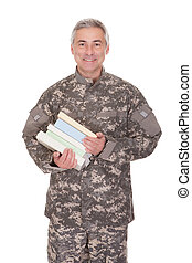 Mature Soldier Holding Stack Of Books Isolated On White...