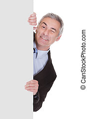 Mature Businessman Pointing At Placard - Mature Businessman...