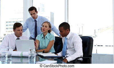 Businesswoman explaining something to her colleagues while...