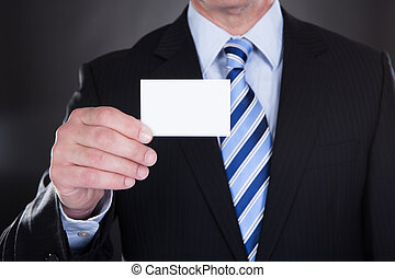 Close-up Of Businessman Holding Visiting Card Over Black...