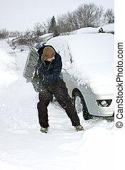 Man shovelling snow - Man shovels snow to get a car out...