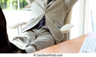 Confident businessman relaxing on his chair in his office
