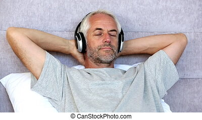 Man relaxing while listening to music with his arms behind...