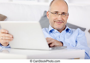 Man with laptop - Smiling man holding laptop while leaning...