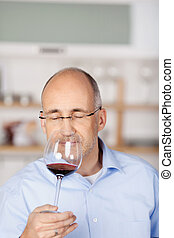 Smelling a glass of red wine - Close up of man smelling a...