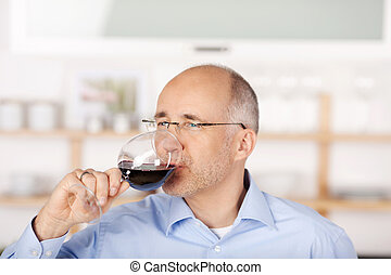 Man drinking red wine - Mid age man drinking red wine at...