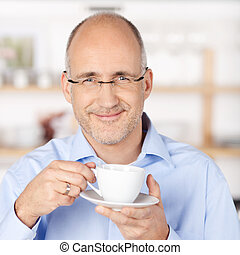Smiling man with a cup of coffee in kitchen - Smiling man...