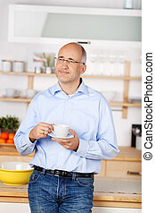 Pensive man in kitchen - Bald man thinking while holding a...
