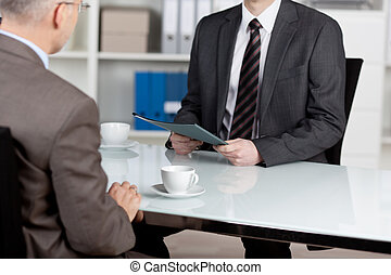 Manager interviewing a male applicant in his office