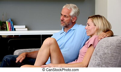 Husband changing channel for his wife sitting in the sofa