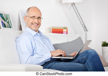 Smiling man with laptop - Smiling man sitting on the couch...