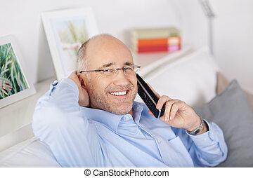 Happy man with phone at home - Happy mature man calling on...