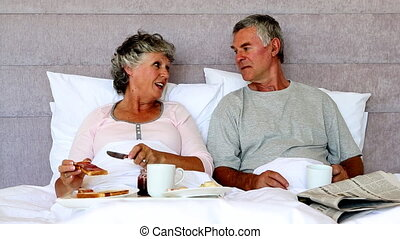 Woman feeding her husband slice of toast in the bedroom at...