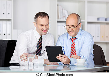 Businessmen with tablet computer - Two businessmen searching...