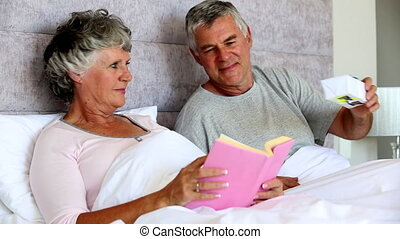 Husband giving a gift to his wife while she is reading a...