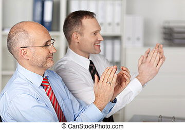 Business people clapping hands during meeting presentation...