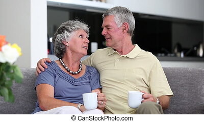 Mature couple chatting together with a cup of coffee on a...