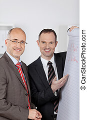 Two businessmen discussing at flipchart