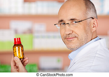 Mature male pharmacist shows the medicine at the drugstore
