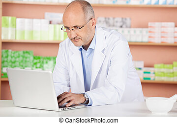 Pharmacist with laptop - Portrait of pharmacist browsing the...