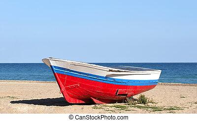 Old boat resting on the beach in Badalona, (Barcelona) Spain.