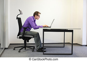 bad sitting posture at laptop .short-sighted business man on...