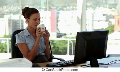 Businesswoman drinking a cup of tea in her office