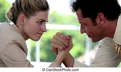 Businesswoman and businessman arm wrestling at the office