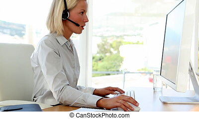 Businesswoman talking on headset an