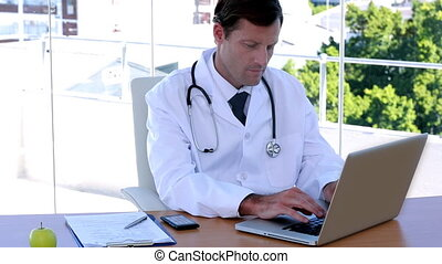 Doctor typing at his desk