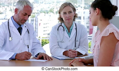 Doctors speaking with patient sitting at desk in office