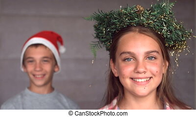 Siblings wearing garland and hat to celebrate christmas in...