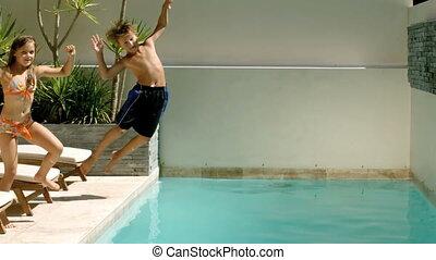 Happy siblings diving into the pool - : Happy siblings...