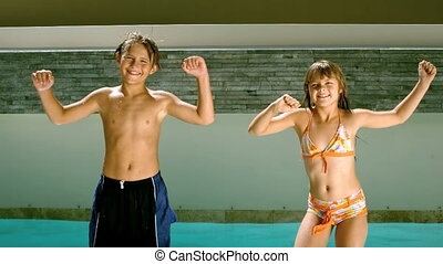 Siblings dancing together in front of the swimming pool in...