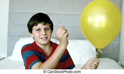 Boy piercing his yellow balloon and getting a fright in slow...