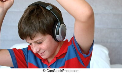 Young boy enjoying music with headphones in slow motion at...